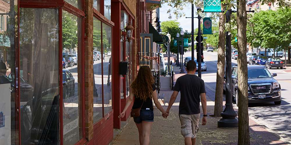 Two people walking through a suburban downtown in Kane County